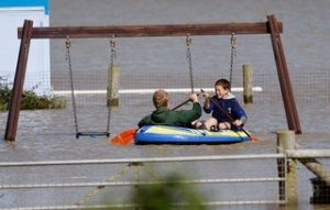 Kids Paddling In Flood