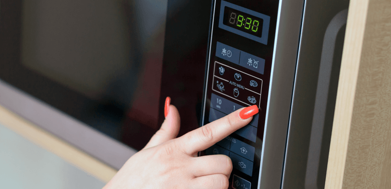 Woman's Hand Pressing Microwave Buttons