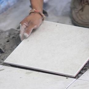 Man Replacing A Loose Floor Tile