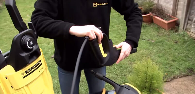 Person Holding Pressure Washer Hose And Spray Trigger