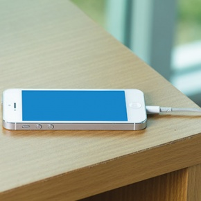 Mobile Phone Charging On Wooden Table