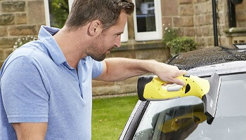Man Cleaning Car With Window Vacuum