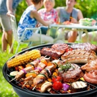 Group Of People Eating Food From The BBQ
