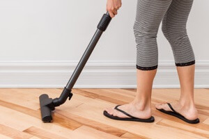 Woman Vacuum Cleaning Wooden Floor
