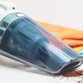 Handheld Vac Sucking Up Coffee Grounds
