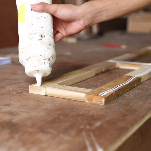 Applying Wood Glue To A Piece Of Wood