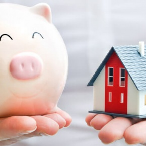 Man Holding Piggy Bank and Toy House