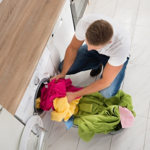 Man Putting Clothes In Tumble Dryer