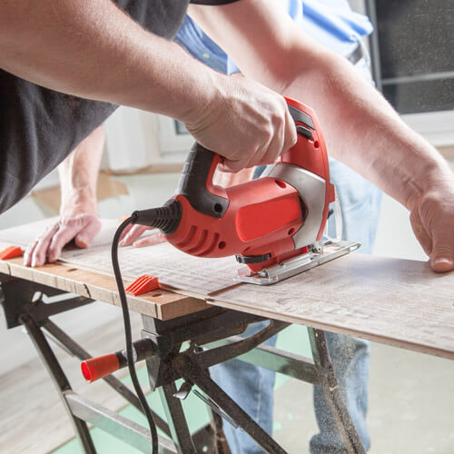 Man Sawing Wood On Workbench