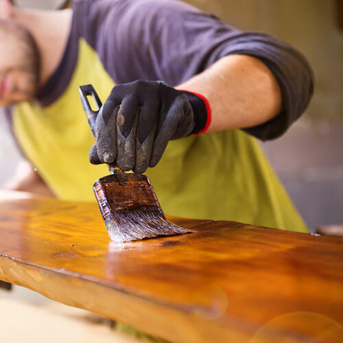 Man Varnishing Plank Of Wood
