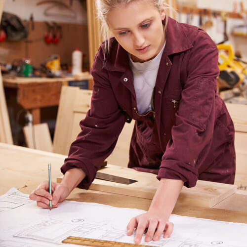 Woman Drawing Out Plans On Workbench