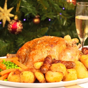 Christmas Dinner On Table With Christmas Tree Behind