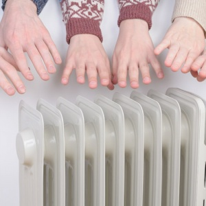 Family Warming Hands On Electric Heater In Winter