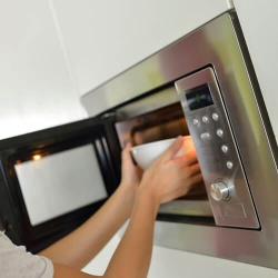 Woman Taking Bowl Out Of Microwave