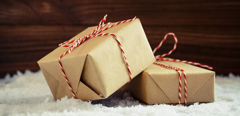 Brown Parcels Tied With Festive String On Snow