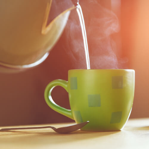 Kettle Pouring Water Into Teacup