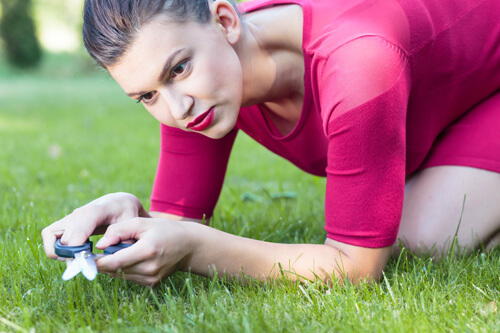 Woman Cutting Grass With Scissors