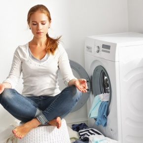 Woman Doing Yoga Fitness Next To Washing Machine