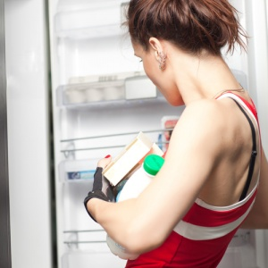 Woman Removing Contents From Fridge