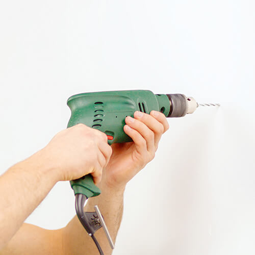 Drill Drilling Into White Wall