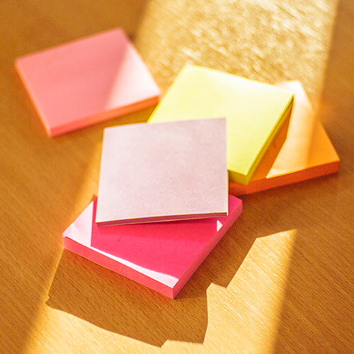 Pile Of Post-It Note Pads On Wooden Surface