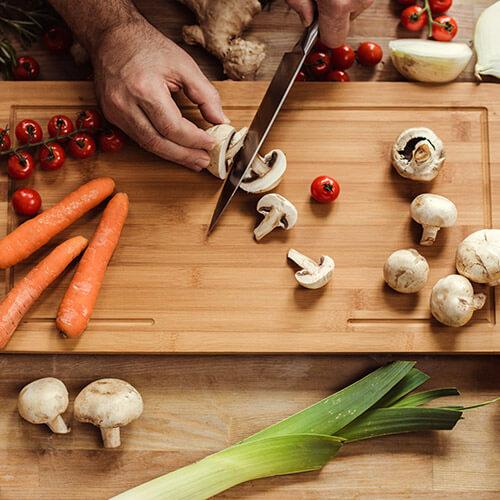 Man Slicing Mushrooms On Chopping Board
