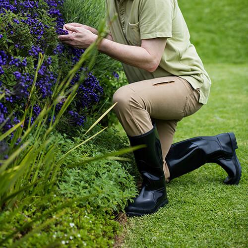 Person Kneeling On Grass In Garden