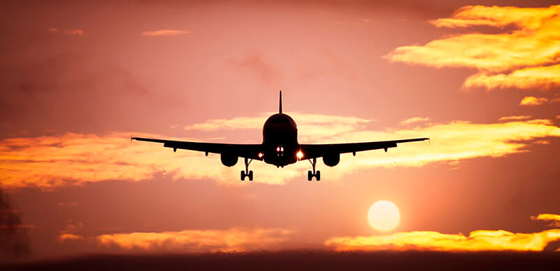 Plane Flying At Sunset
