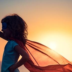 Girl In Hero Pose On Beach