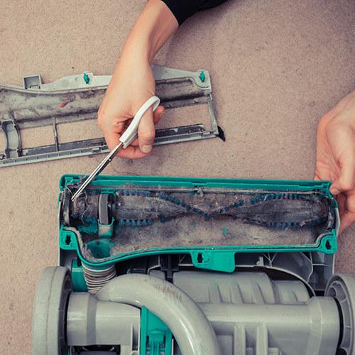 Person Cleaning Vacuum Brushroll With Scissors
