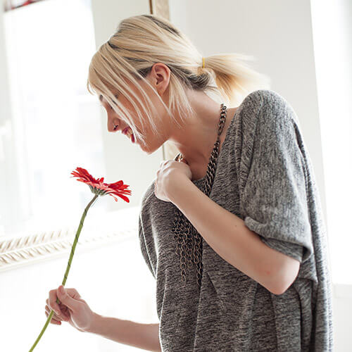 Woman Smelling Red Gerbera Flower