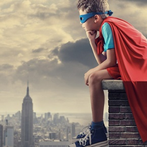 Boy Superhero Sitting On Roof