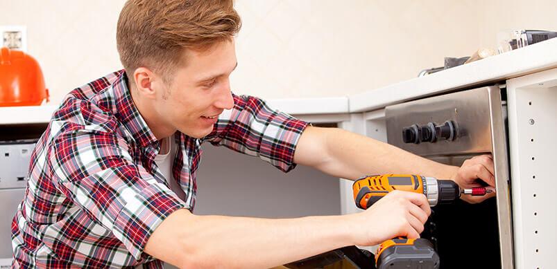 Man Screwing Oven Door With Screwdriver