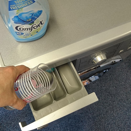 Pouring Fabric Softener Mix Into Washing Machine