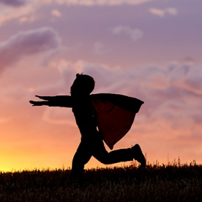 Silhouette Of Child Pretending To Have Flying Superpower
