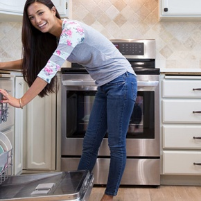 Smiling Woman Loading Dishwasher