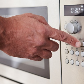 Man Pressing Button On Microwave