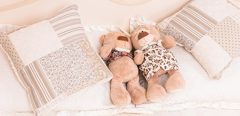 Soft Toys And Cushions On Bed