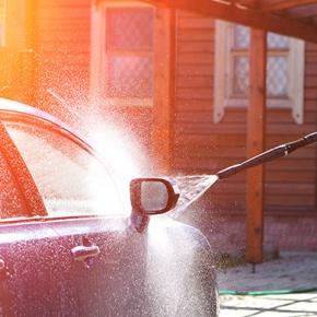 Man Pressure Washing Car On His Drive