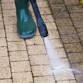 Person Washing Driveway With Pressure Washer