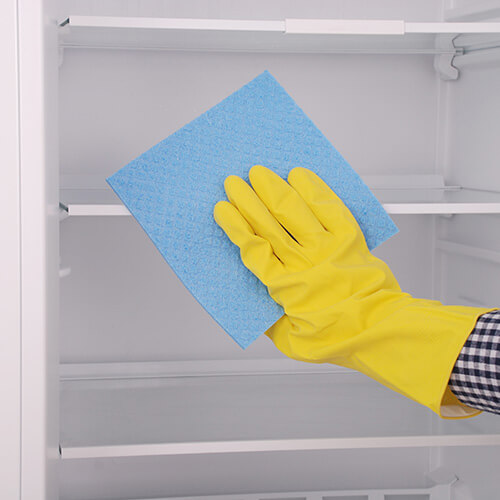 Hand in Rubber Glove Cleaning Fridge