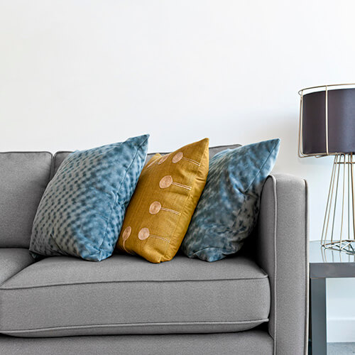 Grey Sofa With Coloured Cushions and Lamp