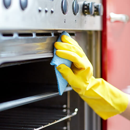 Hand in yellow glove cleaning grill