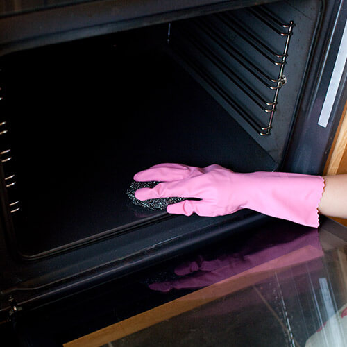 Hand in Rubber Glove Cleaning Bottom Of Oven