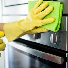 Hands in Rubber Gloves Cleaning Front Of Oven