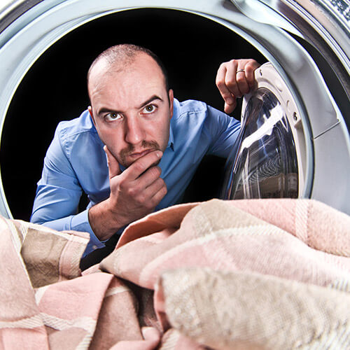 Man Looking Through Washmachine Looking Confused