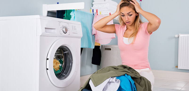Woman Looking Stressed By Tumble Dryer And Clothes Pile