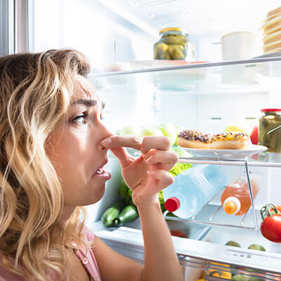 Woman Holding Her Nose By Fridge