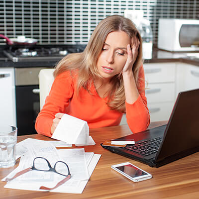 Woman Looking At Bills Looking Stressed