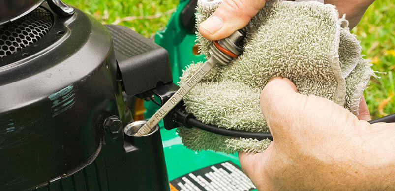Close Up Of Person Checking Lawnmower Oil